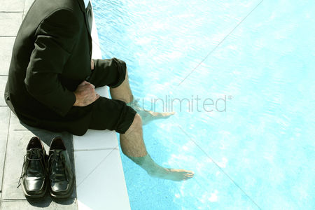 Contemplation : Businessman sitting by the pool side with his legs in the pool