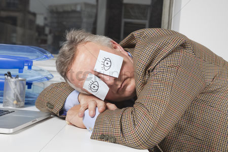 Office worker : Businessman sleeping with sticky notes on eyes at desk in office