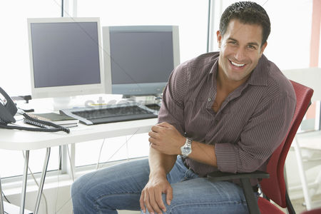 People : Businessman smiling by computers in office portrait