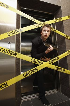 Forbidden : Businessman sneaking out of a cordon taped elevator