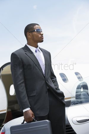 Pocket : Businessman standing beside airplane hand in pocket holding a briefcase