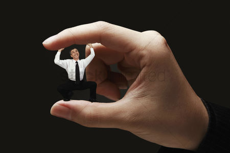 Two people : Businessman standing in between two fingers