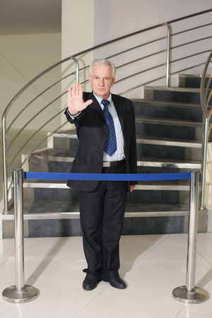 Stairs : Businessman standing in front of stairs and barrier showing stop gesture