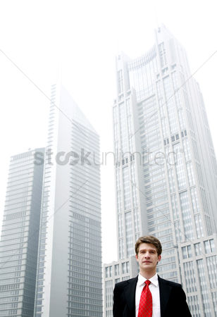 Determined : Businessman standing in front of tall buildings