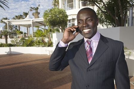 Jacket : Businessman stands holding mobile phone in front of hotel