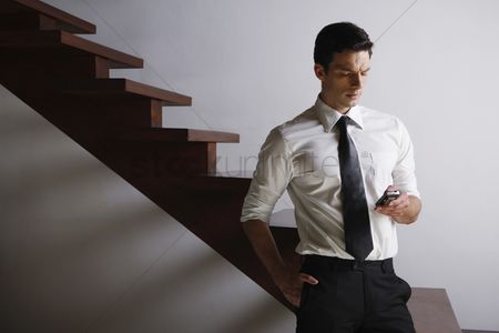 Stairs : Businessman text messaging on the phone