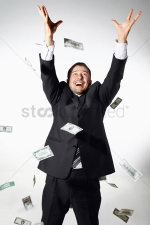 Three quarter length : Businessman throwing money in the air