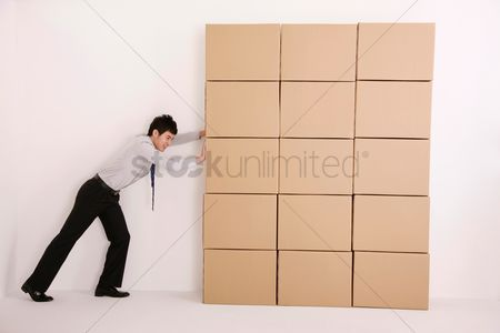 Pushing : Businessman trying to push cardboard boxes