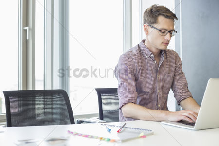 Women : Businessman using laptop at desk in creative office