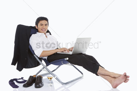 Portability : Businessman using laptop while relaxing
