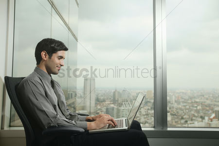Three quarter length : Businessman using laptop