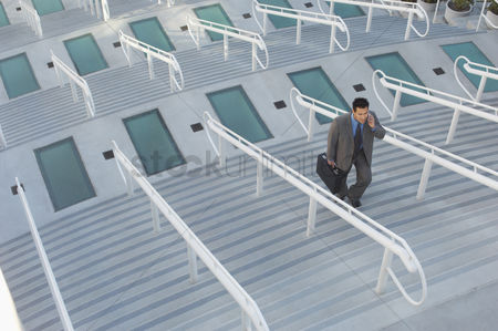 Stairs : Businessman walking up stairs elevated view