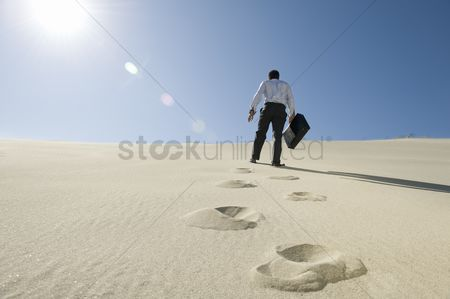 Remote : Businessman walking uphill with briefcase in the desert