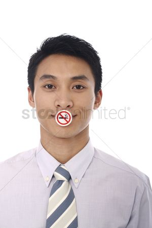 Forbidden : Businessman with a  no smoking  sign covering his mouth