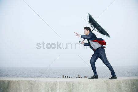 Business suit : Businessman with an umbrella  wind blowing his umbrella away