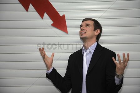 Loss : Businessman with arrow pointing down on him