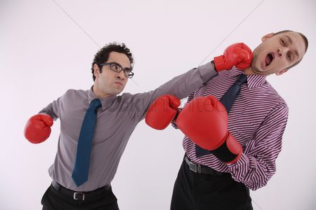 Eastern european ethnicity : Businessman with boxing gloves punching man in the face