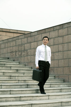 Staircase : Businessman with briefcase walking down the stairs