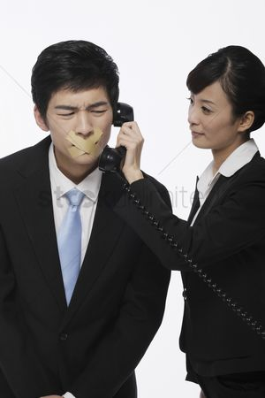 Forbidden : Businessman with his mouth taped  businesswoman holding telephone receiver near his ear