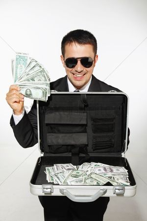 Business suit : Businessman with sunglasses showing a briefcase of money
