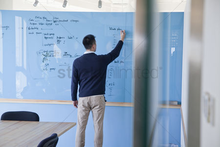 Advice : Businessman writing notes on the glass board