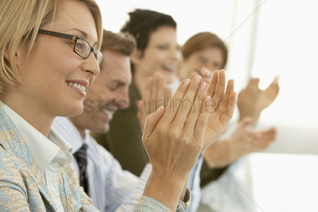 Smiling : Businesspeople clapping in conference meeting