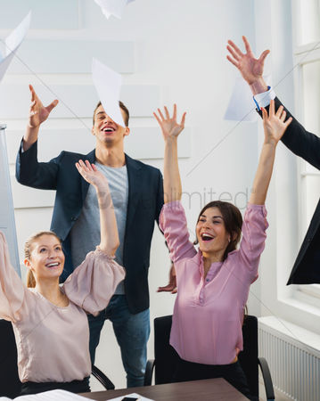 Celebrating : Businesspeople throwing papers in the air at office