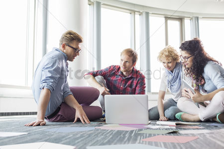 Creativity : Businesspeople using laptop while sitting on floor at creative office