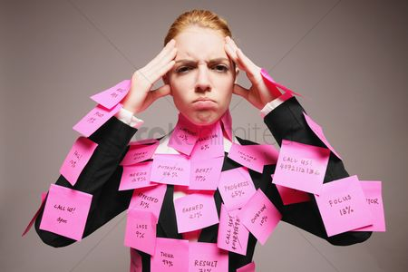 Frowning : Businesswoman covered with adhesive notes having headache