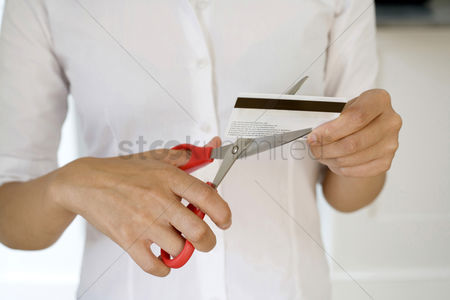 Business suit : Businesswoman cutting credit card