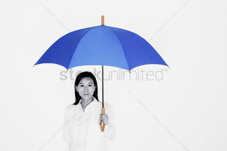 Vision : Businesswoman holding a blue umbrella