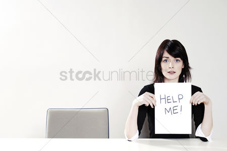 Business : Businesswoman holding a  help me  sign
