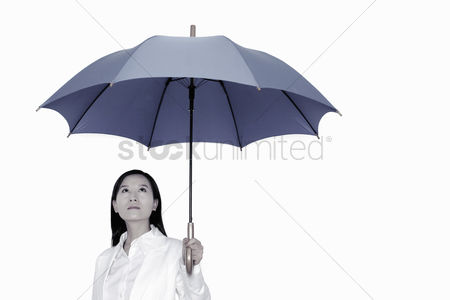 Wondering : Businesswoman holding an umbrella