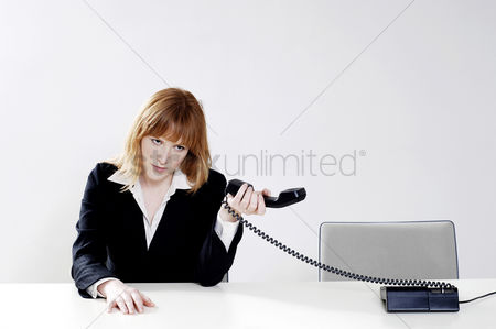 Rage : Businesswoman holding phone receiver away from her ear
