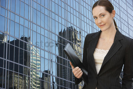 Jacket : Businesswoman holding portfolio outside office building portrait