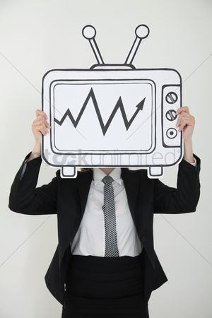 Cardboard cutout : Businesswoman holding television indicating stock market growth over her face