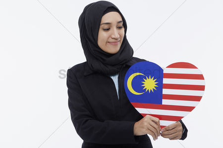 Flag : Businesswoman holding up a heart shaped malaysian flag