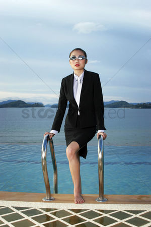 Composed : Businesswoman in goggles climbing out from the swimming pool