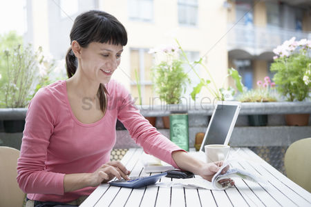 Pink : Businesswoman in pink t-shirt calculating in city garden