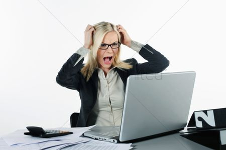 British ethnicity : Businesswoman looking frustrated while using laptop