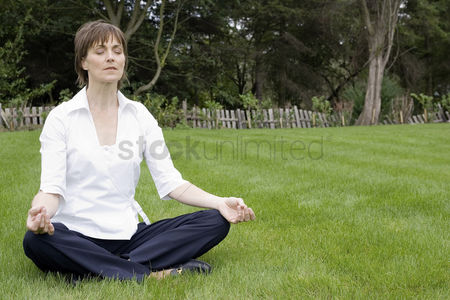 Grass : Businesswoman meditating in the park