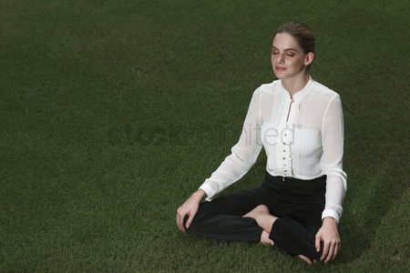 Practising yoga : Businesswoman meditating on the field