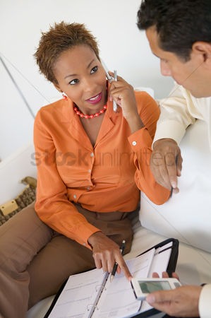 Cell phone : Businesswoman on cell phone working with businessman on sofa