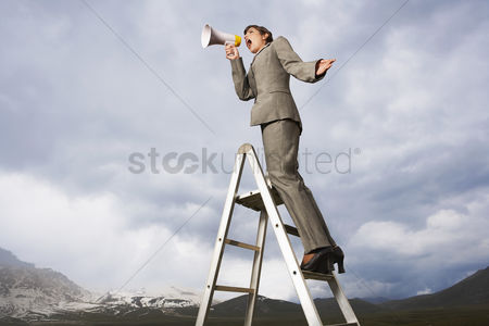 Moody : Businesswoman on ladder in mountain field shouting through megaphone low angle view