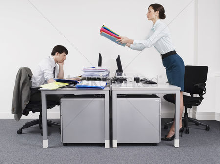 Supervisor : Businesswoman passing off work to male colleague in office