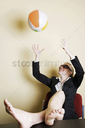 Comfort : Businesswoman playing with beach ball in the office