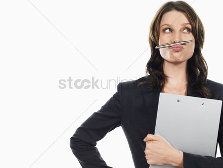 Head shot : Businesswoman pulling funny face with pen