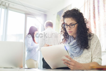 Creativity : Businesswoman reading notepad at creative office with colleagues in background