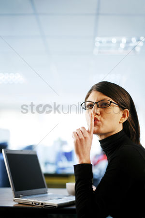Bespectacled : Businesswoman showing hushing sign