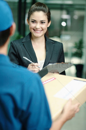 Satisfaction : Businesswoman signing for package